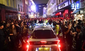 A car tries to drive along a street filled with revellers drinking in the Soho area of London on July 4, 2020