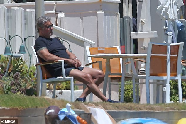 Scenic: Sly looked relaxed as he took in the ocean views while enjoying a refreshment