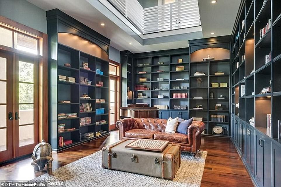 Classy: A study in the home features finished wooden floors and dozens of shelves