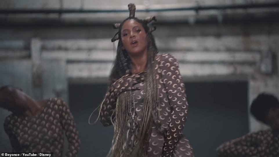 Dancers:The iconic singer is wearing a brown onesie with several small crescent moons printed on it as she dancers with a number of backup dancers