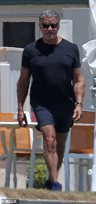 Stroll: The acting icon looked in good spirits as he walked down the beach
