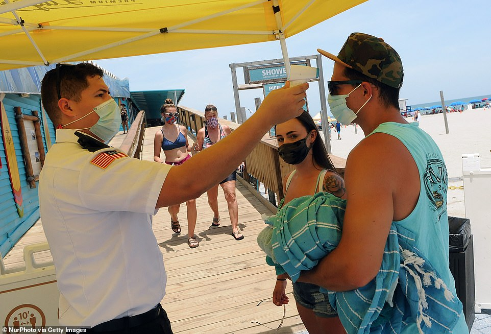 Some Florida beaches, like those in Miami, were closed over the Fourth of July weekend, while others in places Cocoa Beach remained open but required masks and temperature checks (pictured)