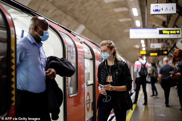 Commuters wearing a face mask travel on TfL Victoria Line underground train carriages, heading towards central London, on June 15