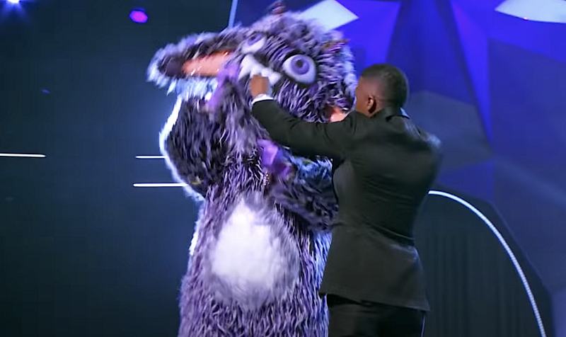 Host Nick Cannon tries to stop the Gremlin from ripping off his own costume on 'The Masked Singer' Season 4. (Photo: Fox)