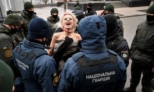 Police officers arrest an activist of Femen movement protesting outside Ukrainian President's to mark the International Day for the Elimination of Violence against Women in Kiev on 25 November 2020.