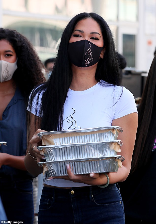 Giving back: Kimora Lee Simmons proved she has a heart of gold as she helped out the residents of Skid Row Housing Trust's Star Apartments in Los Angeles this Tuesday