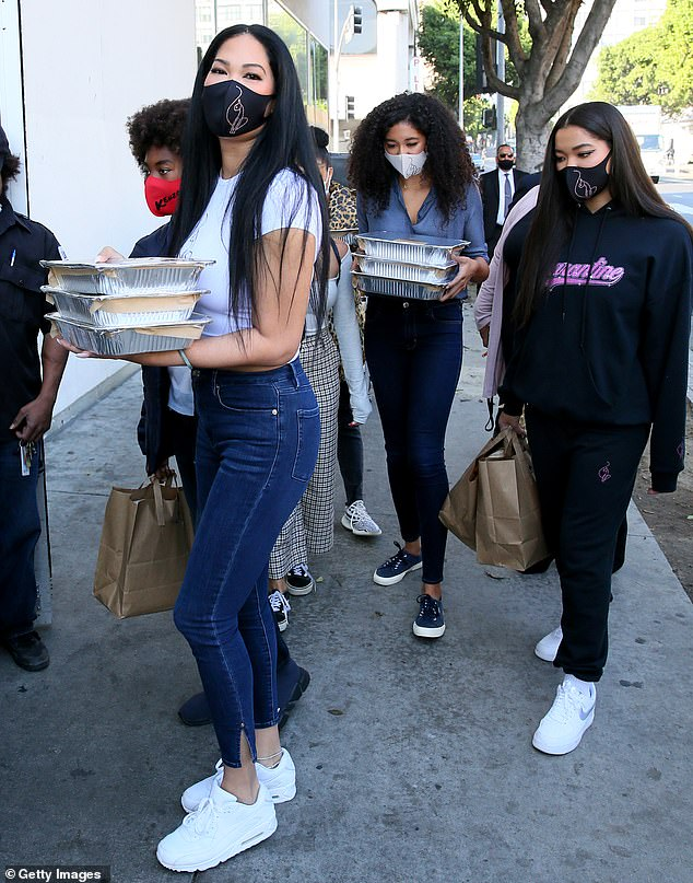 All together now!The Baby Phat founder, 45, carried trays of food into the establishment while followed by her five kids
