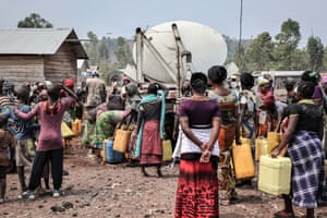 People gather to fill containers from a water truck in Kanyaruchinya on the outskirts of Goma, the capital of eastern DRC's North Kivu province, in 2017. Many neighbourhoods do not have access to running water and rely instead on communal pumps or water trucks.