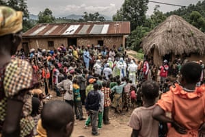 Neighbours and Red Cross burial workers in protective clothing gather outside the home of a family where an 11-month-old girl has died during Congo's Ebola outbreak in the town of Rutshuru in North Kivu province, February 2020.
