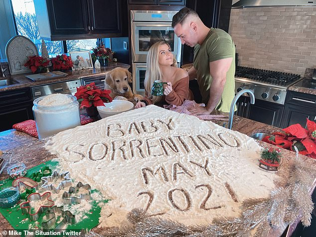 T-shirt time: The happy couple shared kisses from their kitchen amid a scene of baking supplies with 'baby Sorrentino May 2021' scrawled in flour