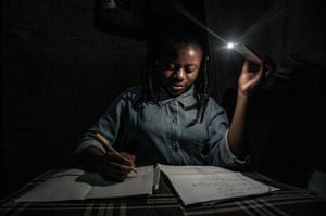 With schools closed during Congo's period of confinement, 13-year-old Marie studies at home by the light of a mobile phone during one of the regular power cuts in Goma in April.