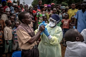 A Red Cross burial worker shows a man how to put on protective gloves before the inspection of the body of an 11-month old girl who died during the Ebola outbreak in the town of Rutshuru in North Kivu province, February 2020. Finbarr O'Reilly