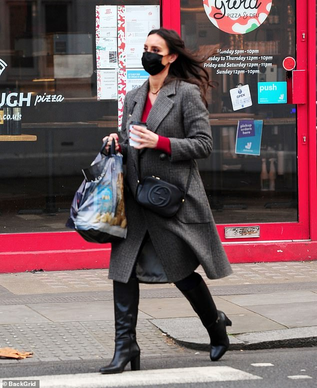 Sleek: The Loose Women panellist looked effortlessly stylish as she strolled along in knee-high boots while keeping warm with a long grey checked coat