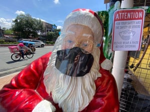 A Santa Claus figure with a face mask and a face shield is at a store in Manila in September.