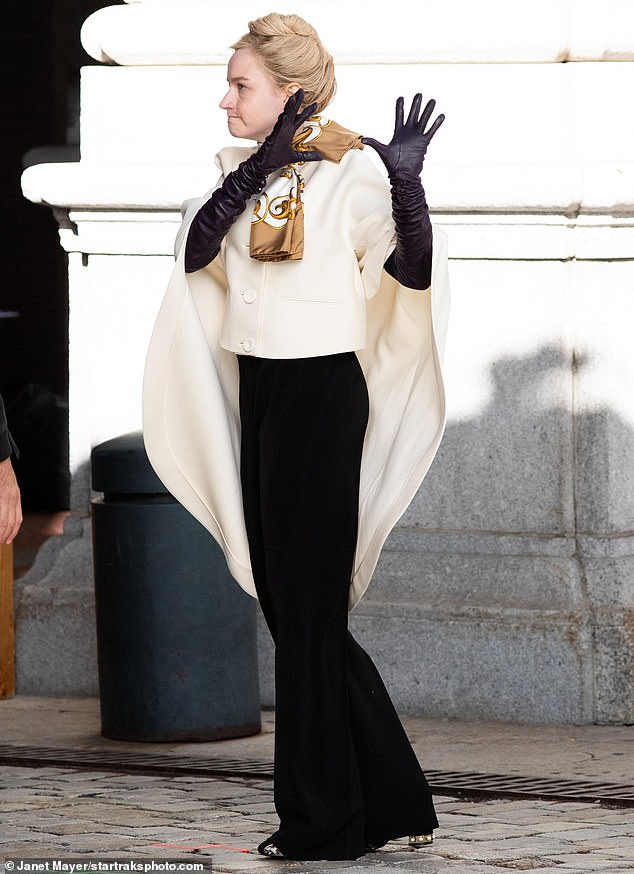 In character: The blonde beauty was elegantly dressed in a white caped jacket paired with a flowing set of black slacks; she accessorized with long leather gloves and a printed scarf while keeping her normally flowing blonde hair in a tight bun