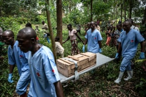 Red Cross workers bury an 11-month-old girl who died in the town of Rutshuru during the Ebola outbreak, February 2020.