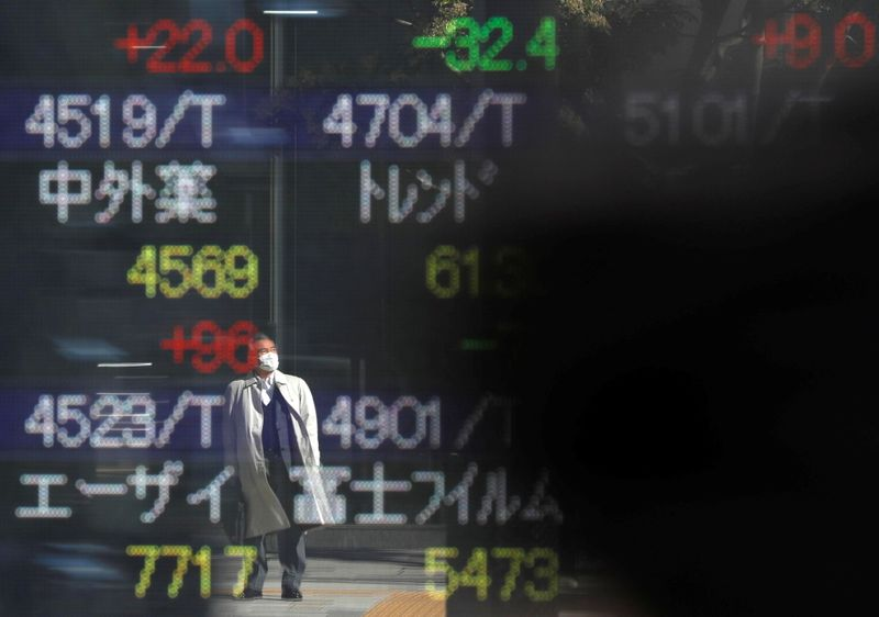 © Reuters. A man wearing a protective face mask is reflected on a stock quotation board outside a brokerage, amid the coronavirus disease (COVID-19) outbreak, in Tokyo