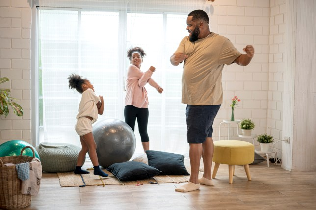 African father and his two daughter morning exercise at home.