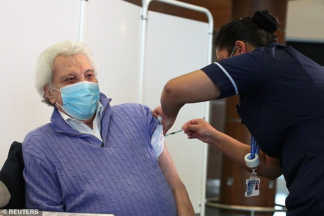 Each vial could contain two extra doses of the vaccine, it was revealed yesterday. Above is entertainer Lionel Blair, 92, getting his vaccine in Epsom, Surrey, on Wednesday