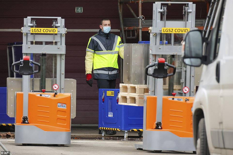 An employee at Pfizer's manufacturing plant in Puurs, Belgium - where Britain's first batches of the Covid jab was shipped from - works with containers of dry ice