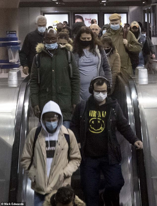 Commuters pictured wearing face masks at Canada Water station in London on the Jubilee line in November this year