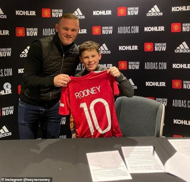 Proud dad: Casually dressed in jeans and a black top under a matching gilet, proud dad Wayne also posed alone with his son as they held up his number 10 football jersey