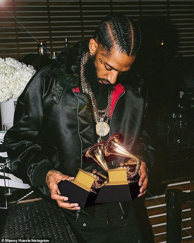 Holding his Grammys: Nipsey's trademark portfolio was worth $913K and he also had pricey personal items like gold pendant chains and Rolex watches