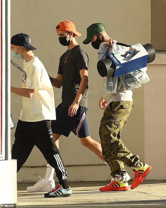 Shopping: David Beckham was spotted buying workout gear from a Dick's Sporting Goods store with his sons - Romeo, 18, and Cruz, 15 - in Miamion Tuesday