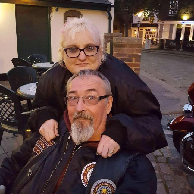 Tracy and Bob pictured smiling in a car park, Tracy is hugging Bob as he sits in his wheelchair