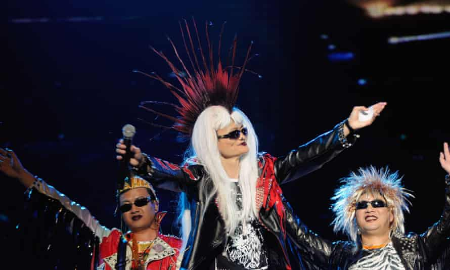 Jack Ma, in a leather jacket, sunglasses  and a wig giving him a Mohican haircut combined with long blonde hair, gestures to the crowd in a rock-star pose