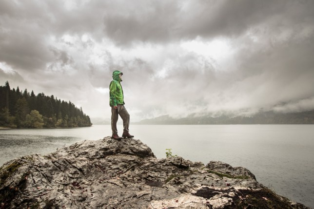 Man standing on a rock beside a dramatic mountain lake after a hike in the rainy, gloomy day. Active lifestyle, outdoor activities, moods and emotions concept. ; Shutterstock ID 331803140; Department: -