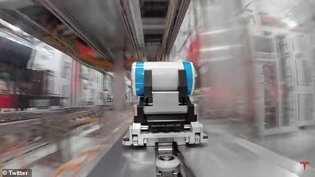 The one-minute clip shows the white and blue battery moving through different assembly stages with the help of armed and wheeled robots