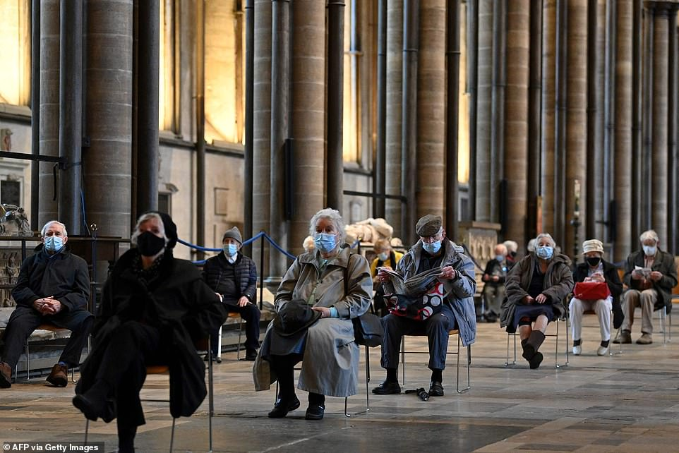 Britons sit socially distanced after receiving a dose of a Covid-19 vaccine at Salisbury cathedral today