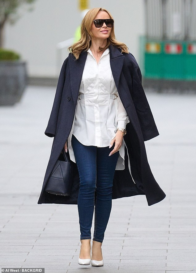 Looking good:Opting for a white blouse and skinny jeans, Amanda, 49, turned heads as she made her daily pilgrimage across a desolate Leicester Square after leaving the studio