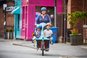 27 May – A family cycles past independent shops in Chorlton, south Manchester