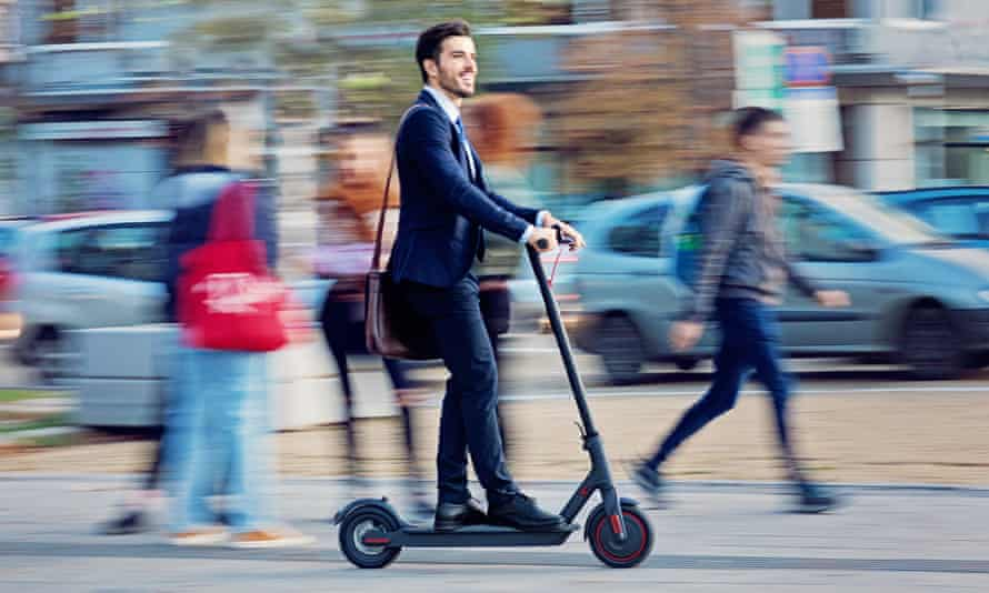 Businessman riding electric scooter in the city