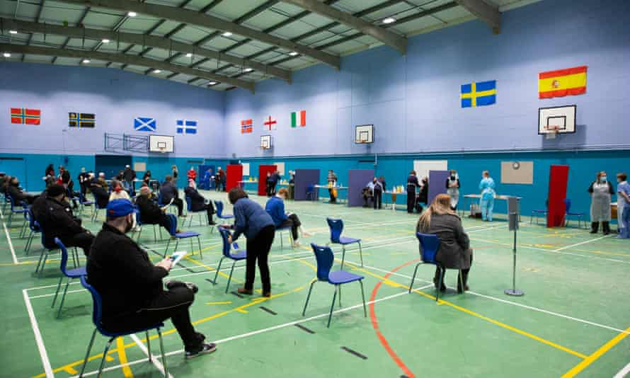 People wait for vaccinations in a school sports hall in Thurso, on the north coast of Scotland.