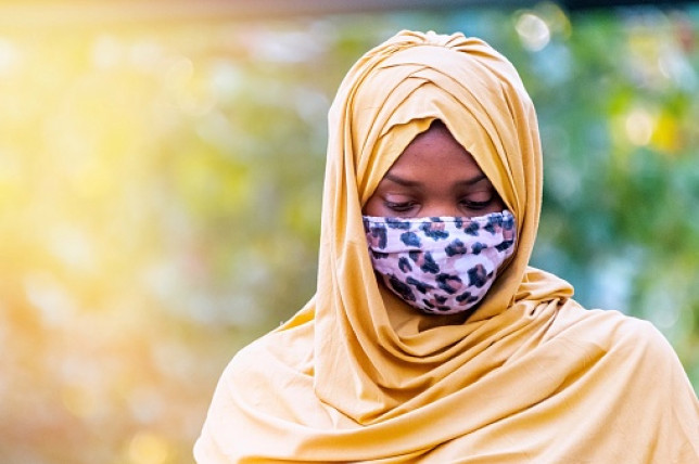Pensive Young black muslim woman looking away wearing a protective face mask