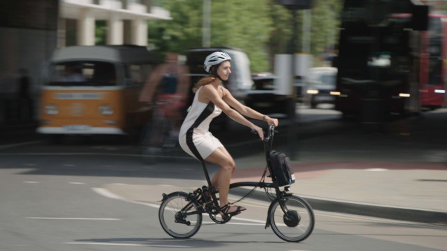Woman cycling to work on an electric Brompton