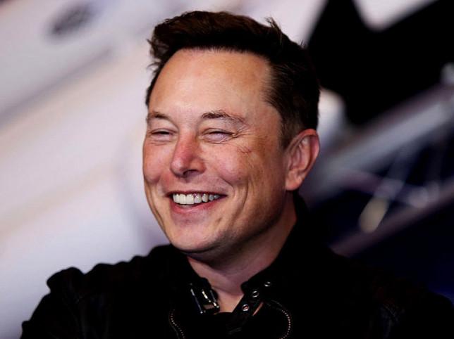 Elon Musk smiles at the camera
