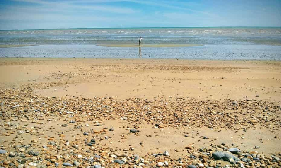 Person on a sandbank in Sandwich bay