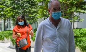 Nigel Skea and wife Agatha Maghesh Eyamalai arrive at the State Court in Singapore on February 26, 2021, for sentencing in a case of violating Covid-19 coronavirus regulations.