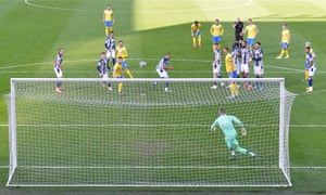 Referee Lee Mason (sixth right), with his hand to his whistle in his mouth, watches as Brighton's English defender Lewis Dunk (5R) scores from a free-kick which following a VAR decision was ruled out, and then in, and then finally out again.