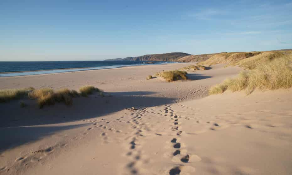 Footprints leading across pristine sandy beach of Sandwood bay,