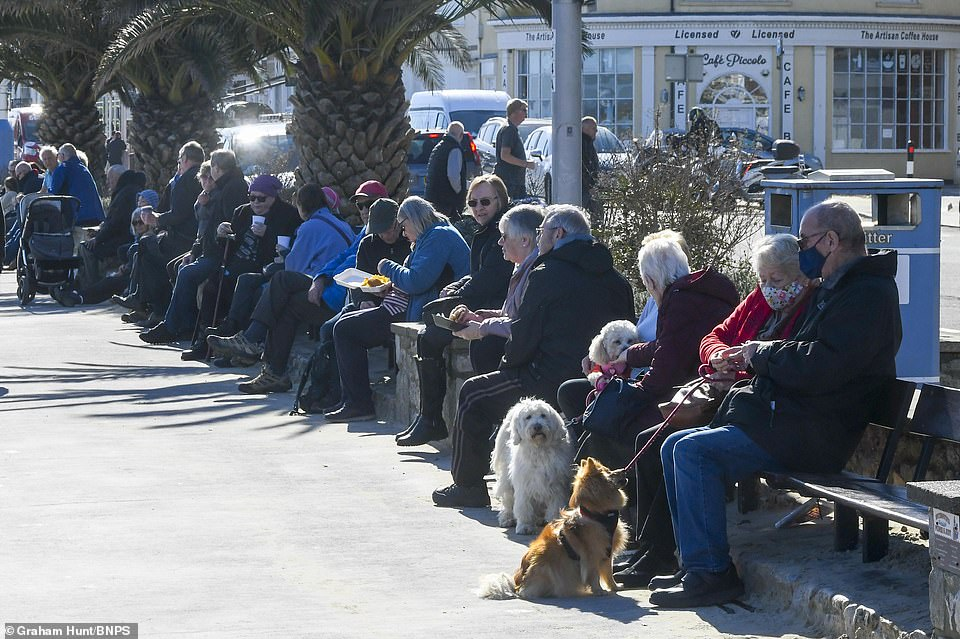 The public enjoyed the clear blue skies and warm sunshine as they sat on the seafront benches at Weymouth in Dorset this afternoon