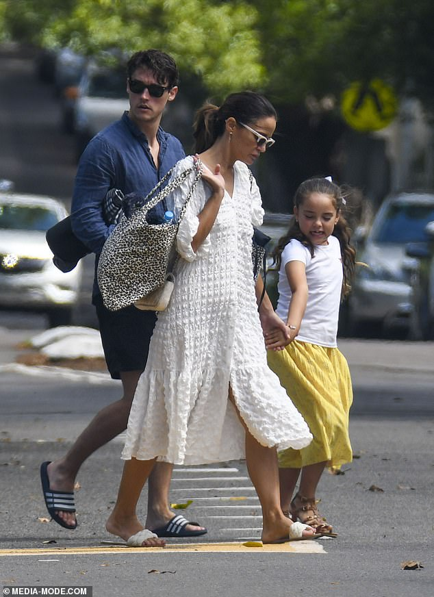 Out and about: Jodi carried two bags on her shoulders while holding her daughter's hand as the trio walked to the park
