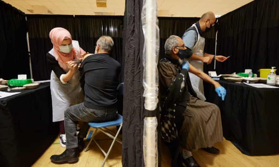 Members of the local community receive their vaccinations at the East London Mosque