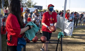 Team member disinfects footballs in between rounds at the Super Bowl Experience, ahead of the NFL Super Bowl LV in Tampa, Florida.