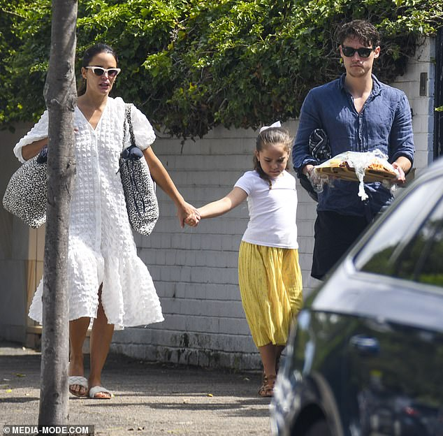 Accessories: She teamed her ensemble with a pair of white sandals and concealed her gaze behind designer sunglasses