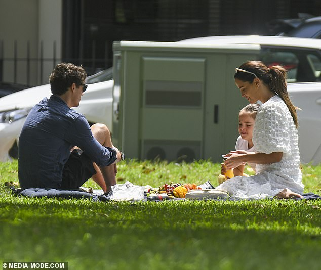 Family outing: The couple relaxed on a picnic rug while Aleeia sat nearby